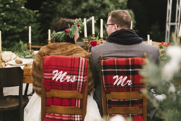 Bride and groom sitting on wedding chairs with Mr and Mrs blankets
