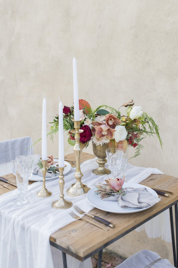 High candles and winter flower arrangement on wedding table