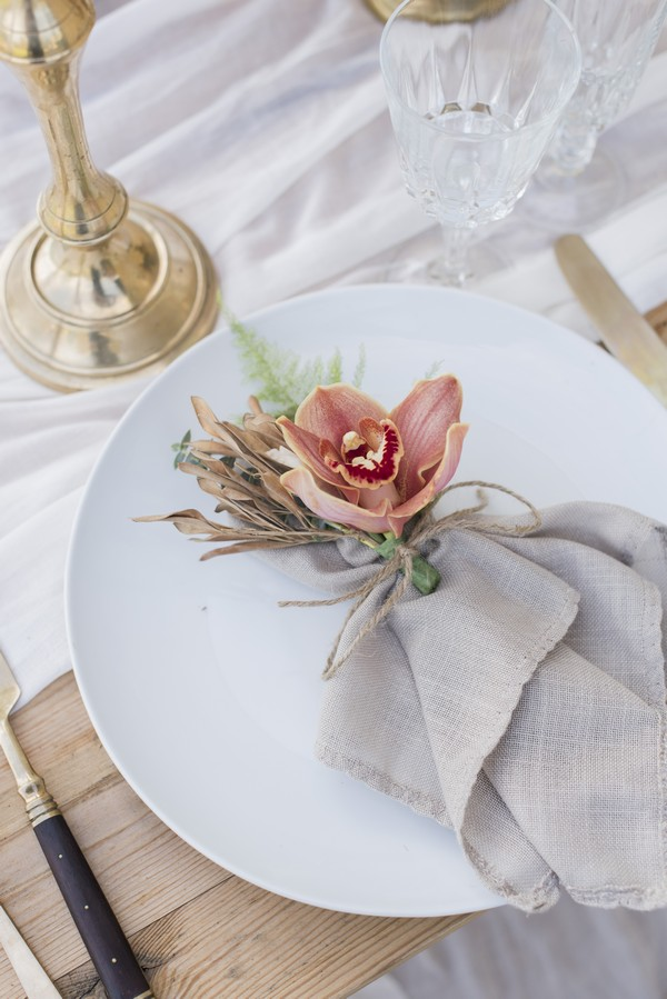 Flower and napkin on plate at wedding place setting