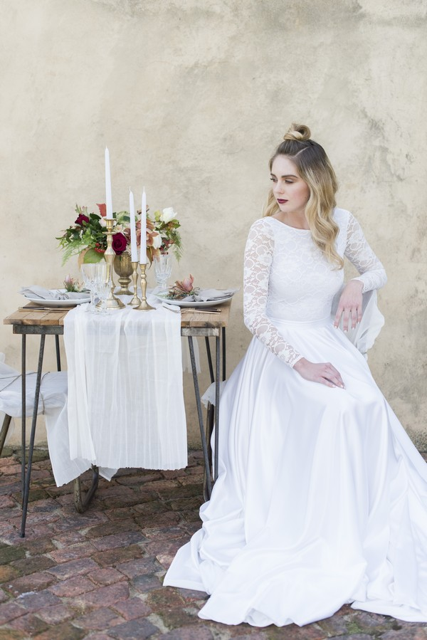 Bride sitting at small wedding table