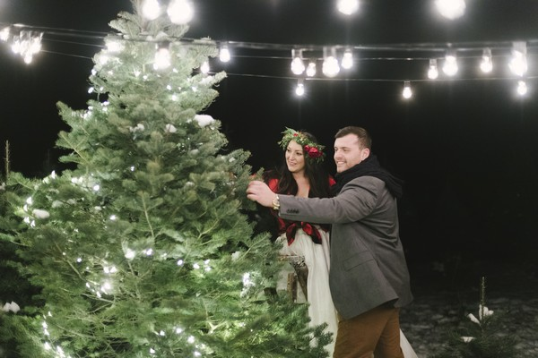 Bride and groom decorating Christmas tree
