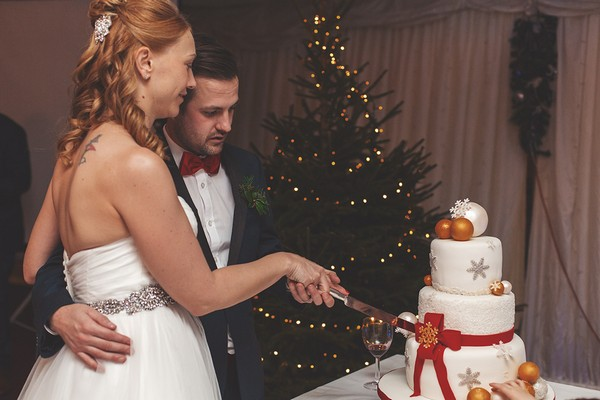 Bride and groom cutting Christmas wedding cake