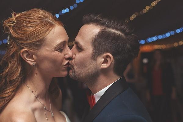Bride and groom kiss on dance floor