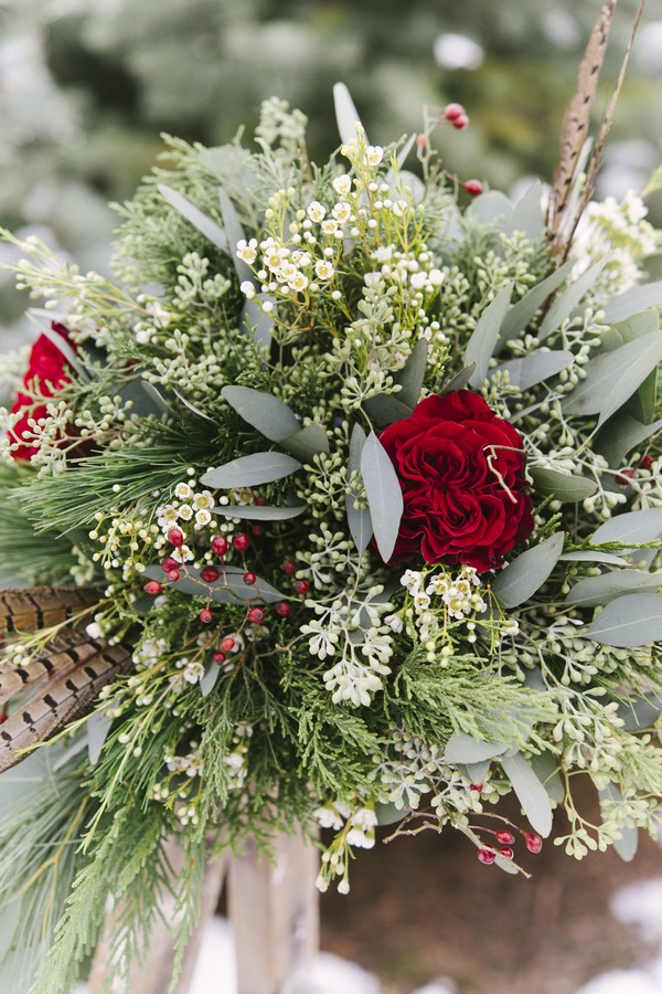 Close up of winter wedding bouquet with rose and foliage