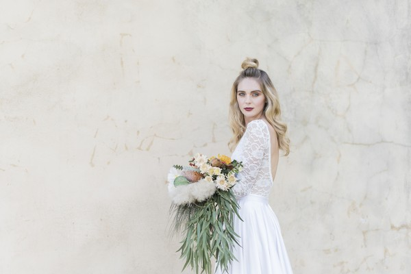 Bride holding bouquet with trailing foliage