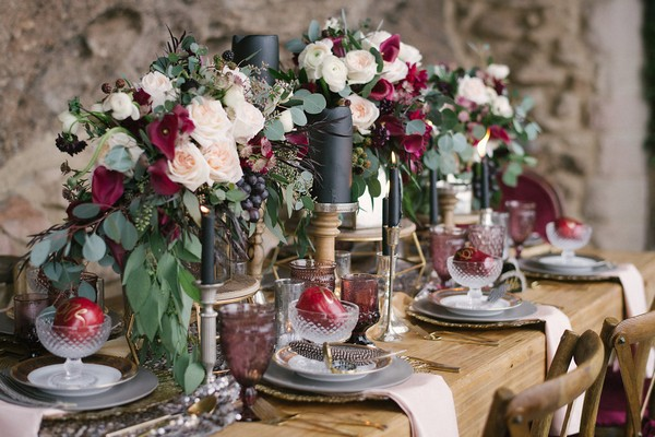 Long wedding table with red and white floral centrepiece