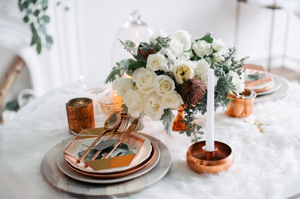 Copper wedding table decorations on white fur tablecloth