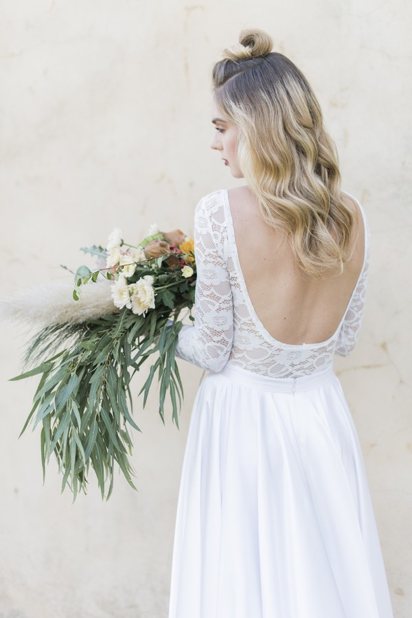 Bride wearing open back wedding dress holding large trailing bouquet