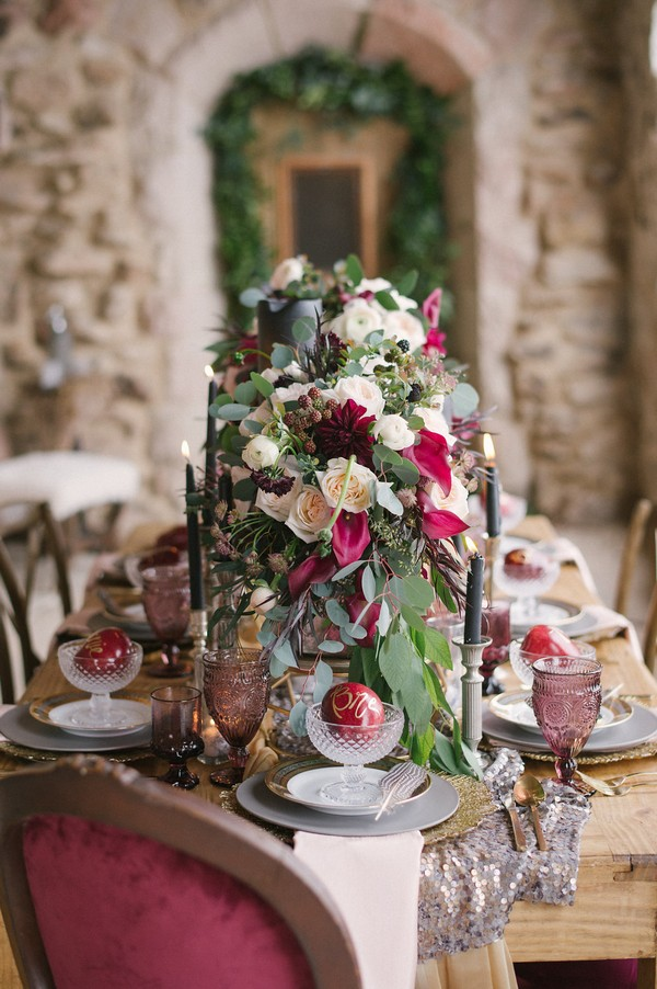 Red and white flowers with foliage down centre of wedding table