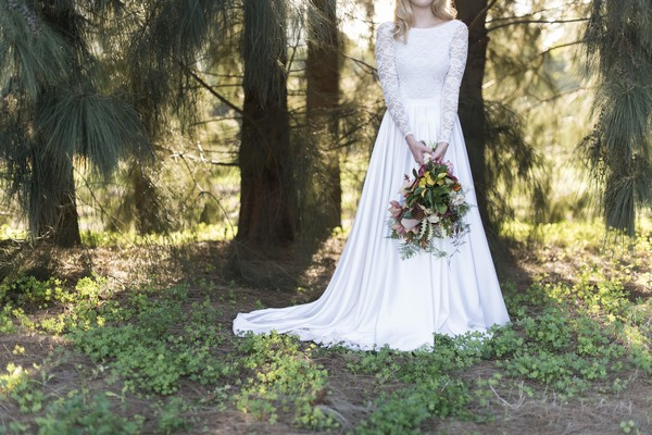 Bride holding large trailing bouquet in front of her