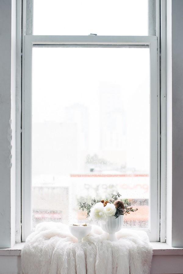 White vase of flowers on window ledge