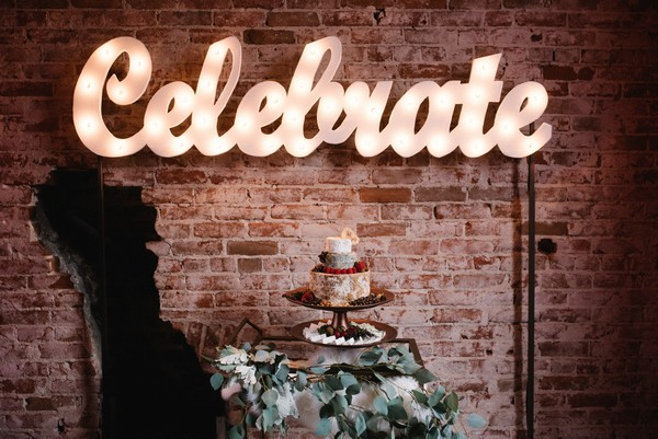 Neon celebrate sign above cheese stack wedding cake