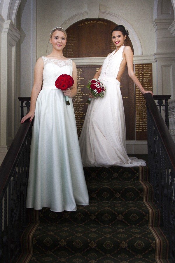 Brides on Stairs Holding Winter Wedding Bouquets with Red Roses