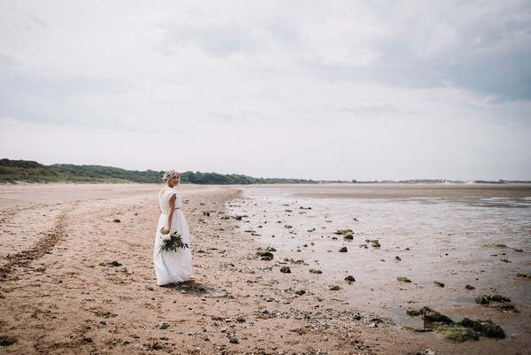 Bride walking on beach in Cumbria