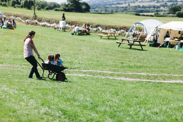 Woman pushing children in wheelbarrow across field at festival wedding