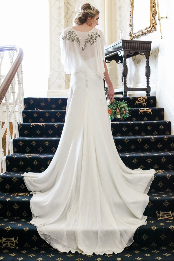 Bride standing on stairs with dress flowing down steps