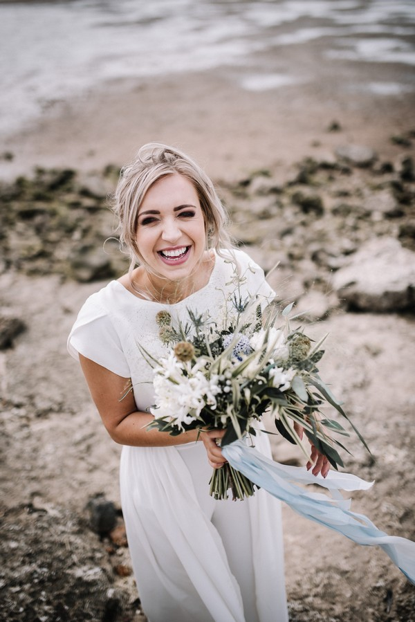 Bride smiling and holding bouquet