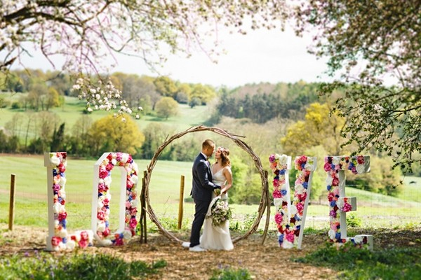 Bride and groom in middle of flower LOVE letters