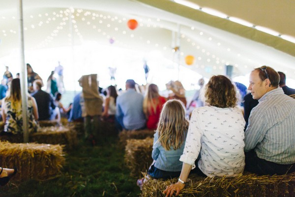 Wedding guests sitting on straw bales for wedding ceremony