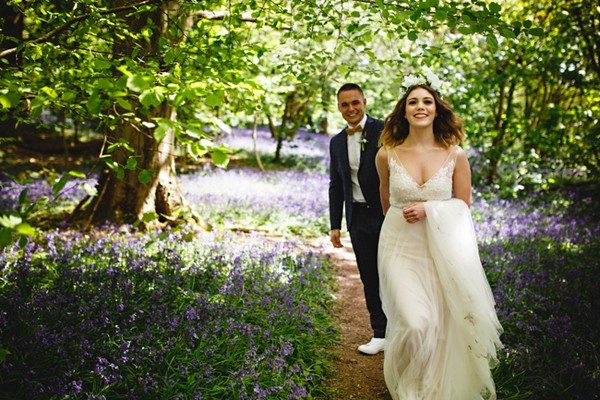 Bride leading groom through woods