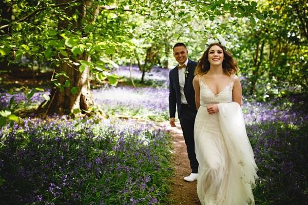 Bride leading groom through woods