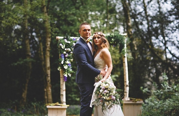 Bride and groom in woodland with wedding arch