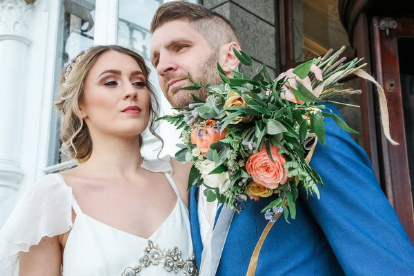 Bride holding bouquet with arm around groom's shoulder