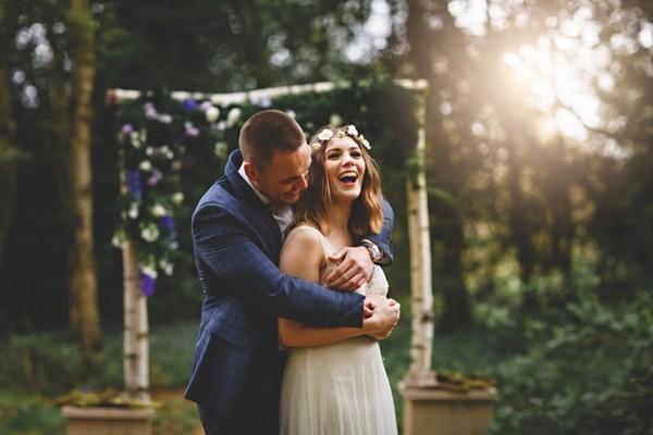 Groom hugging laughing bride from behind