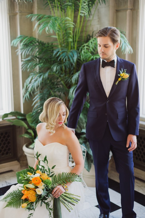 Groom standing next to bride sitting on chair
