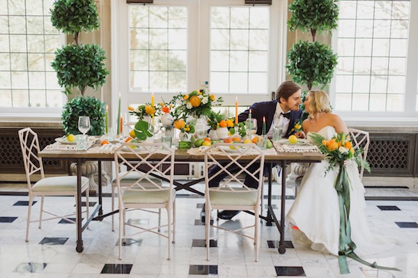 Bride and groom sitting at wedding table with citrus wedding styling