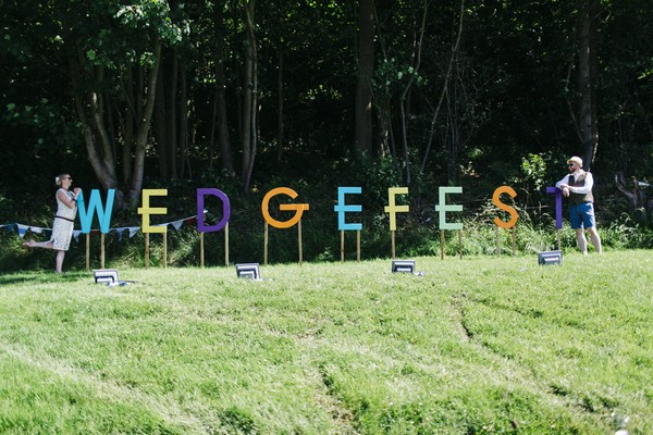 Bride and groom at either end of Wedgefest sign