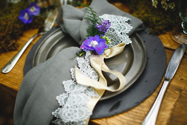 Dark styled wedding place setting with purple flower
