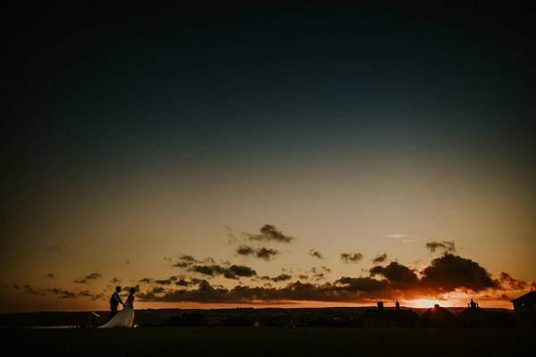 Bride and groom walking at sunset - Picture by Dan Ward Photography
