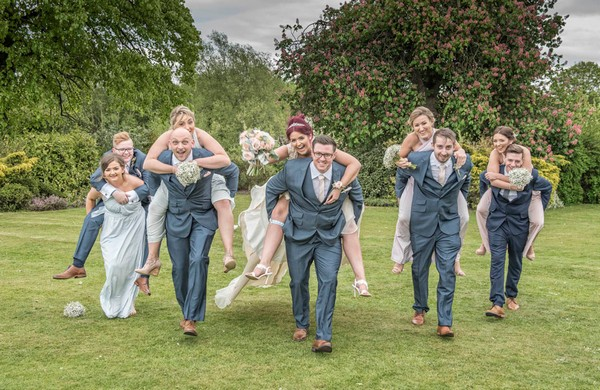 Groomsen giving bridesmaids piggyback ride - Picture by Image-i-Nation Photography