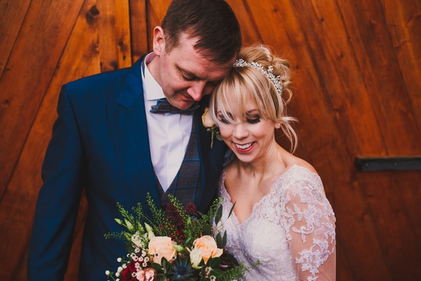 Bride smiling as groom rests his head on hers - Picture by The Struths