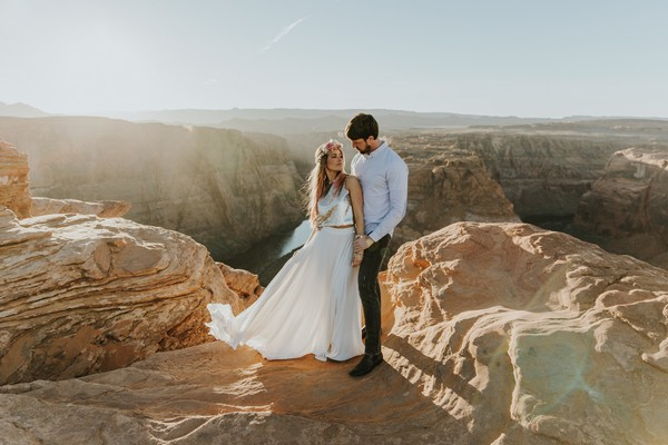 Bride and groom on rocks at the top of a mountain - Picture by Natalie J Weddings