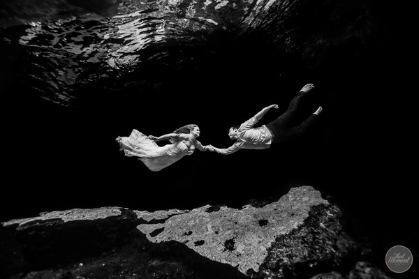 Bride and groom holding hands underwater - Picture by That Moment Photo