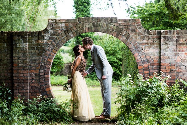 Bride and groom kissing in circular hole in wall - Picture by Nicola Norton Photography
