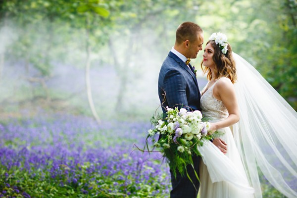 Bride and groom next to bluebells