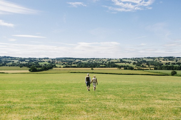 Bride and groom walking across field at Lower Hill Farm