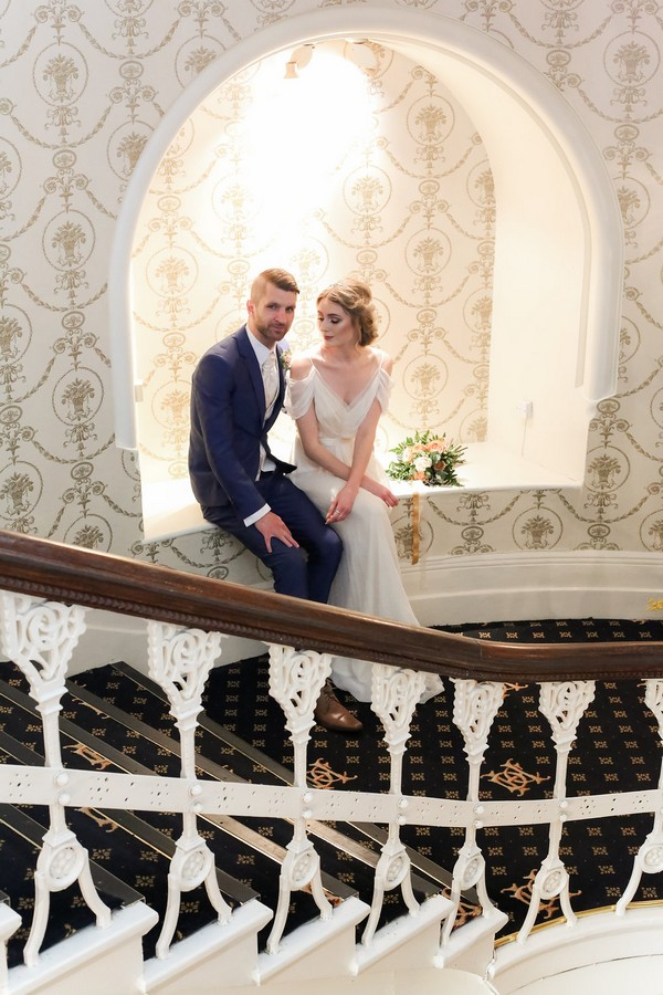 Bride and groom sitting in alcove by stairs of The Duke of Cornwall Hotel