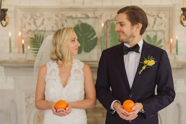 Bride and groom holding oranges