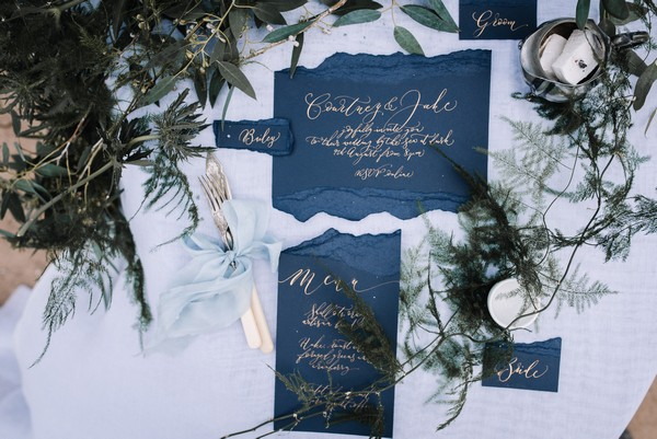 Blue wedding stationery with gold calligraphy lettering