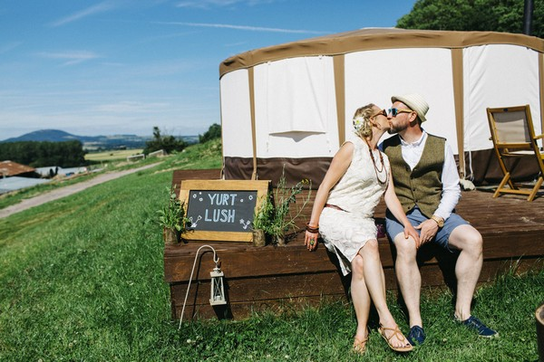 Bride and groom kissing in front of yurt