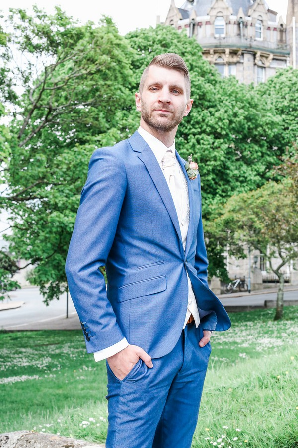 Groom in blue suit with hands in pockets