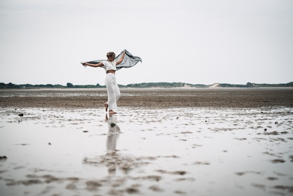 Bride wearing bridal trousers and top holding out shawl on beach