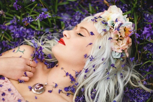Bride laying on ground covered in purple confetti