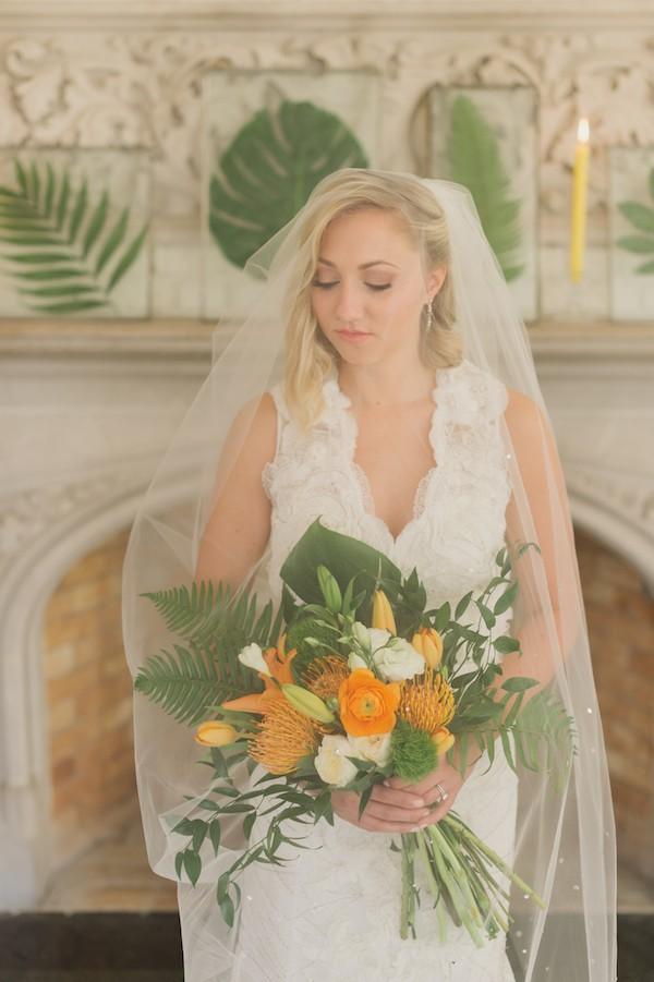 Bride holding bouquet under veil