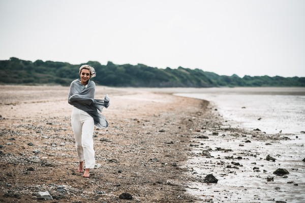 Bride wearing bridal trousers and top walking on beach with shawl wrapped around her