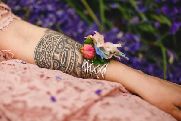 Tattoo and wrist corsage on bride's arm